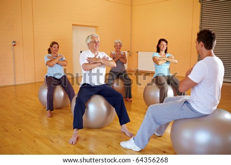 Group in gym doing fitness exercises on exercise ball