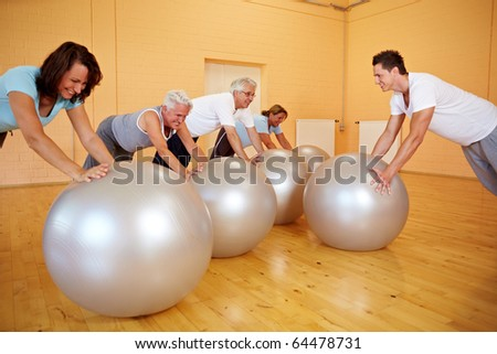 Group in gym doing pushups on exercise ball - stock photo