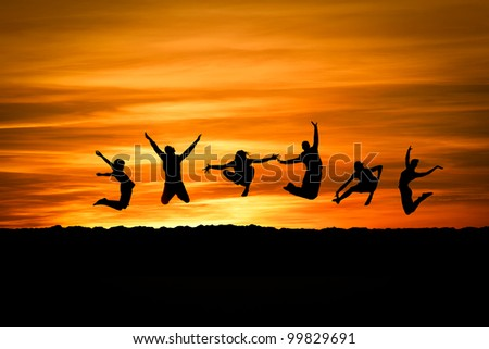 group jumping in sunset at beach - stock photo