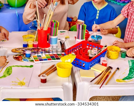 Group kids hands holding colored paper and glue on table in kindergarten . - stock photo