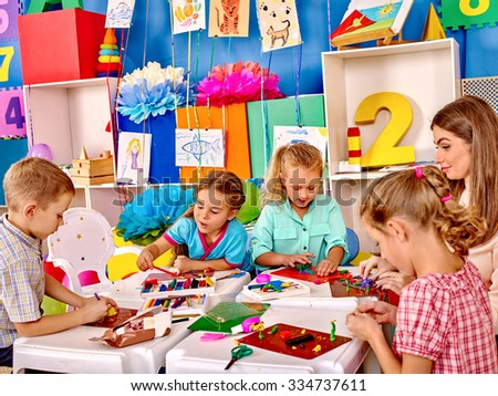 Group kids holding colored paper and glue on table in kindergarten . - stock photo