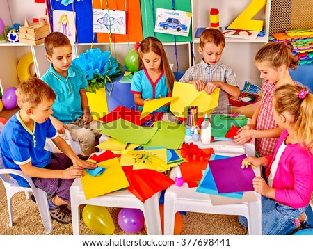 Group kids holding colored paper on craft lesson in kindergarten . - stock photo