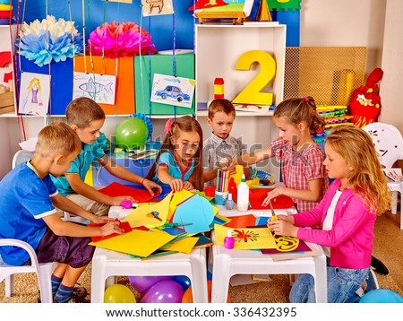 Group kids learning and holding colored paper and glue on table in kindergarten . - stock photo
