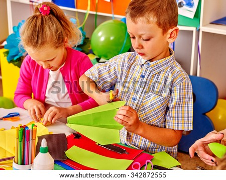 Group kids make  paper origami on table in kindergarten . - stock photo