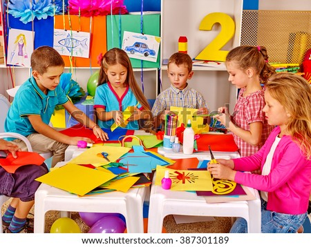 Group kids together engaged in creativity on colored paper  in kindergarten . - stock photo