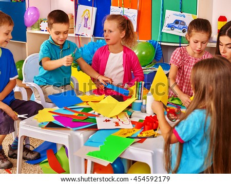 Group kids with techer keeps colored paper on table in primary school . Education in primary school. - stock photo