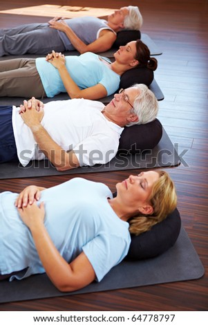 Group laying relaxed on the floor of a gym - stock photo