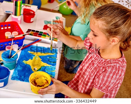 Group little girl with brush painting on table in  kindergarten . Top view. - stock photo
