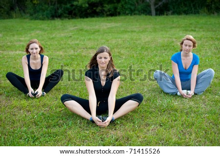 Group meditation - three cute girls meditates outdoor on a green grass field in park - stock photo