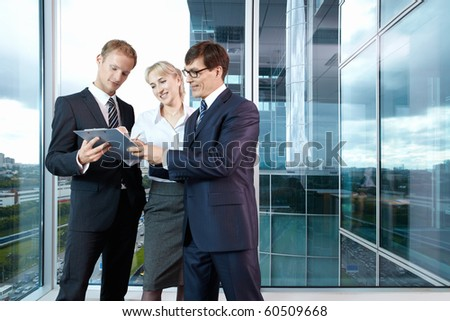 Group members are discussing something in the background of a large window in the office - stock photo