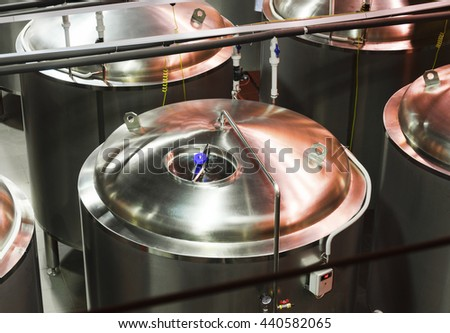 Group metal tanks for liquid products. Taken from above. Poor lighting. - stock photo