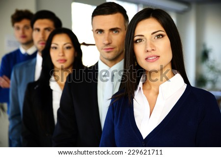 Group of a business people standing lined up in the office - stock photo