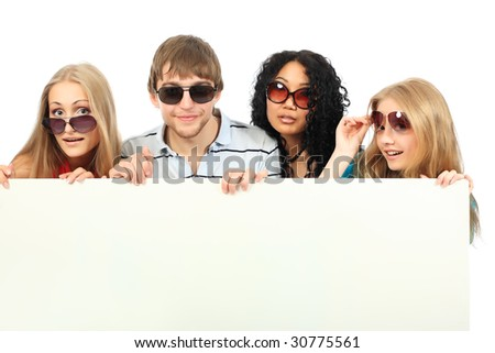Group of a cheerful young people holding a billboard with empty space for your ad. - stock photo