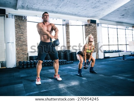 Group of a man and woman workout with kettle ball at gym - stock photo