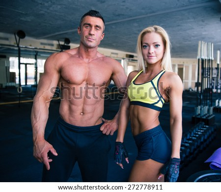 Group of a muscular man and fit woman in gym - stock photo