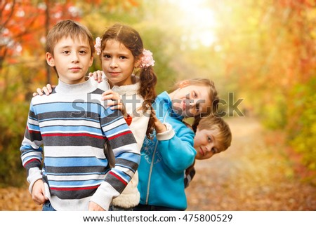 Group of a school aged friends in an autumn park