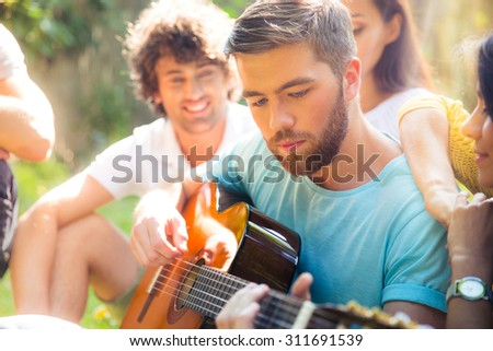 Group of a students with guitar resting outdoors - stock photo