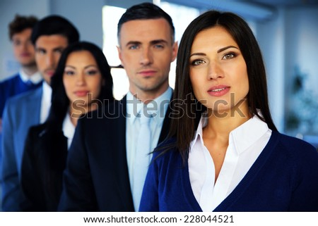 Group of a young businesspeople looking at camera - stock photo