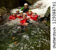 GROUP OF ACTIVE YOUNG PEOPLE DURING A CANYONING EXPEDITION IN ECUADORIAN RAINFOREST  - stock photo