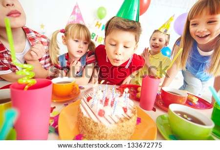Group of adorable kids gathered around birthday cake with candles - stock photo