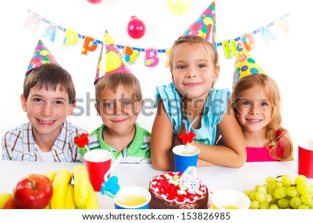 Group of adorable kids having fun at birthday party with birthday cake