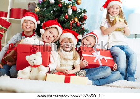 Group of adorable kids in Santa caps looking at camera while sitting by xmas tree - stock photo