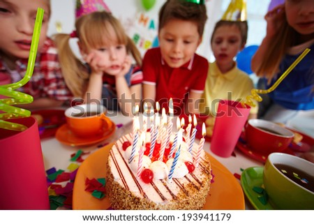 Group of adorable kids looking at birthday cake with burning candles - stock photo