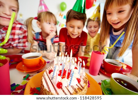 Group of adorable kids looking at birthday cake with candles - stock photo