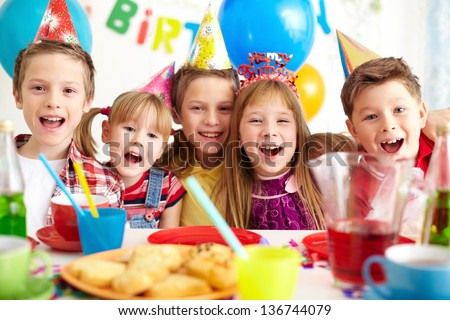 Group of adorable kids looking at camera at birthday party - stock photo