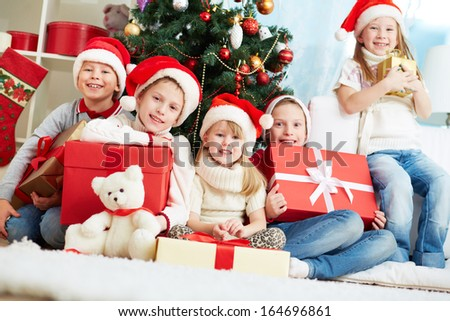 Group of adorable kids with presents looking at camera while sitting by xmas tree - stock photo