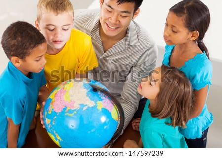 group of adorable students with teacher looking at the globe - stock photo