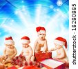 Group of adorable toddlers in Christmas hats packing presents - stock photo