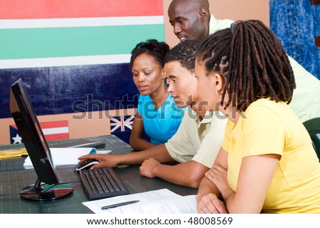 group of adult african american students learning computer together