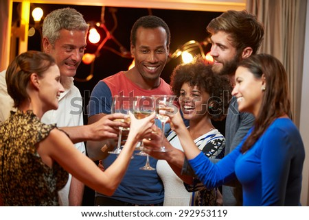 Group of adult friends at party making a toast - stock photo