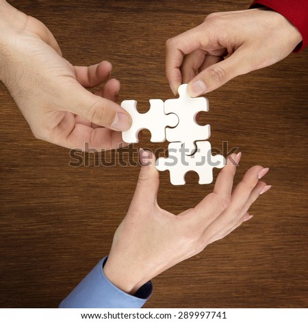 group of adult hands male and female holding jigsaw pieces shot from above looking down - stock photo