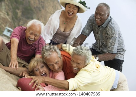 Group of adult multiethnic friends playing American football on the beach - stock photo