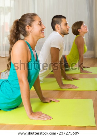 Group of adult people having yoga class in sport club - stock photo