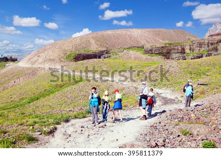 Group of adults with children  walk on the trail  to the Hidden Lake. Glacier National Park, Montana, US - stock photo