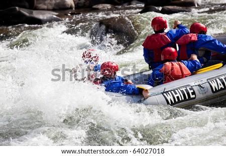 Group of adventurers in an inflatable dinghy in the white water of a fast moving river - stock photo