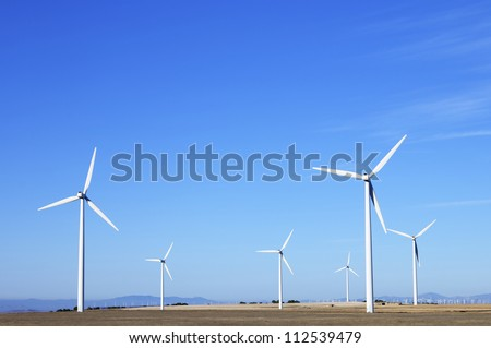 group of aligned windmills for electric power generation alternative - stock photo