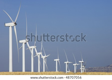 Group of aligned windmills with yellow field - stock photo