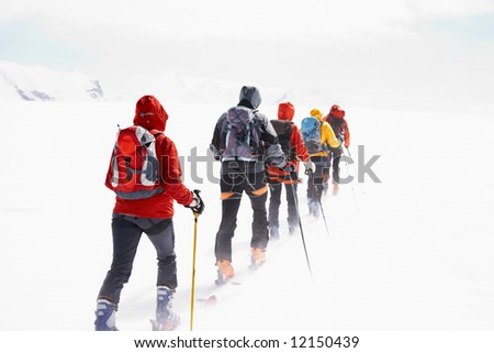 Group of alpine touring skiers on the big Verra Glacier; in background the peaks of Castore and Polluce. MonteRosa, Swiss-Italy border. - stock photo