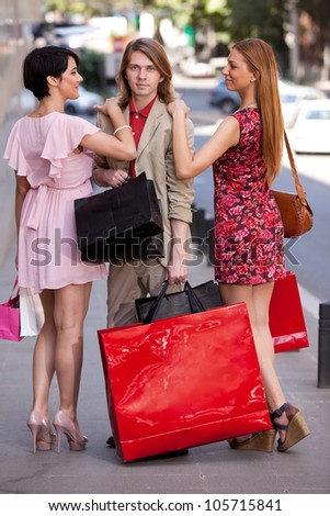 Group of an handsome young man with two beautiful women with colorful shopping bags on the street. Concept for temptation - stock photo