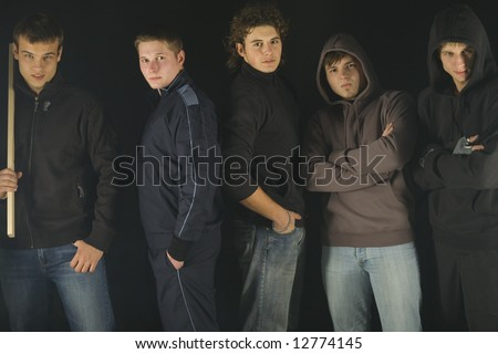 Group of angry hooligans. They are looking at camera and standing in dark place. Front view - stock photo