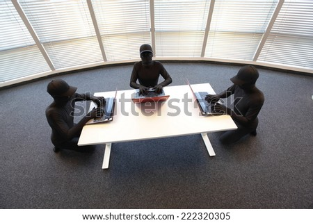 group of anonymous hackers in black costumes working with computers in office - stock photo