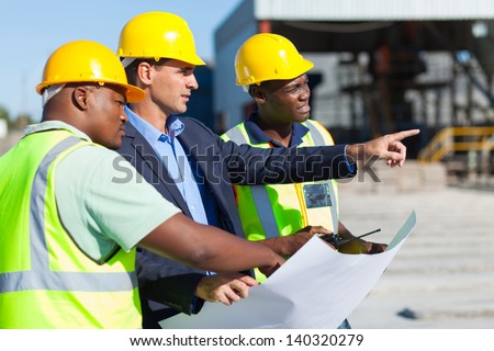 group of architect and construction workers on site with blue print - stock photo