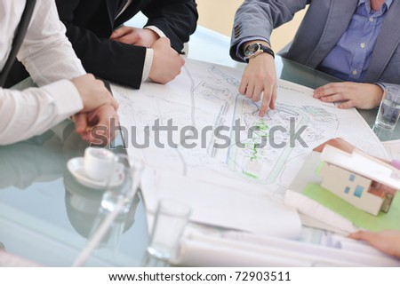 group of architect business team people on meeting looking model and desing of new real estate house - stock photo
