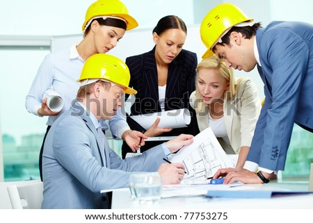 Group of architects discussing draft of new construction - stock photo