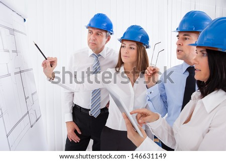 Group Of Architects Discussing New Project On Whiteboard - stock photo