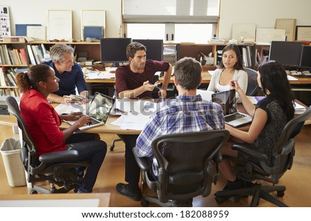 Group Of Architects Meeting Around Desk - stock photo